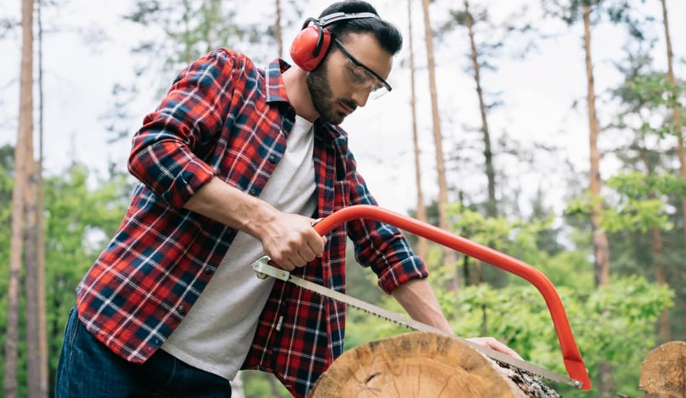 A Man Using Bow Saw for Cutting Wood